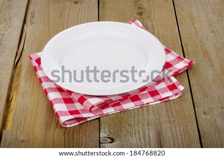 Empty plate on red-white checkered tablecloth in an old wooden table - stock photo