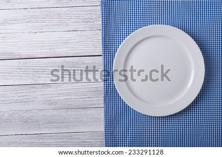 Empty plate on tablecloth on wooden table - stock photo