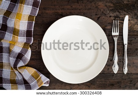 Empty plate on tablecloth on wooden table