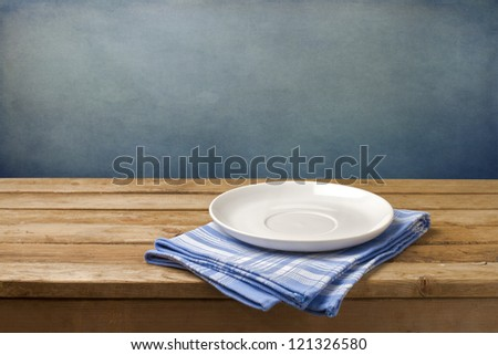 Empty plate on tablecloth on wooden table over grunge blue background - stock photo