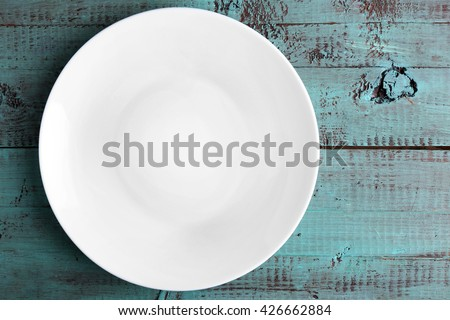 Empty plate on wooden background, top view - stock photo