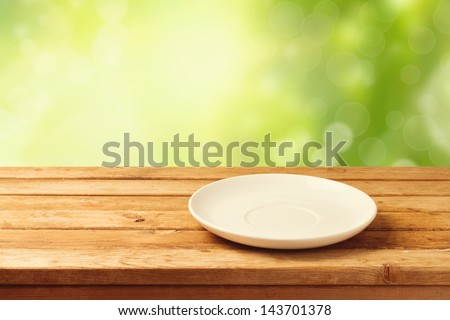Empty plate on wooden table over bokeh background - stock photo