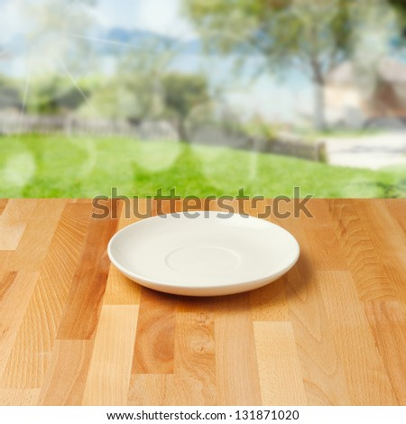 Empty plate on wooden table over nature background - stock photo