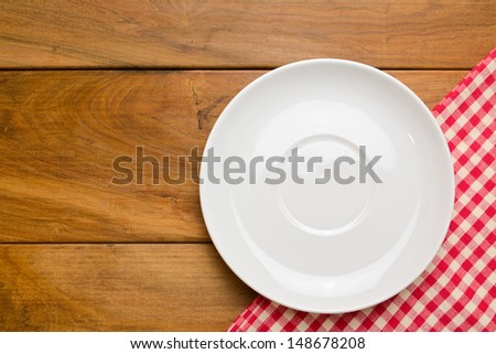Empty plate on wooden tabletop with tablecloth - stock photo