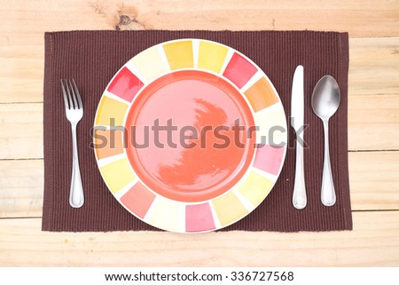 Empty plate on wooden tabletop with tablecloth