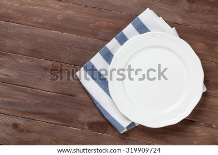 Empty plate over wooden table background. View from above with copy space - stock photo