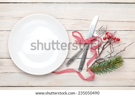 Empty plate, silverware and christmas decor. View from above over white wooden table background - stock photo
