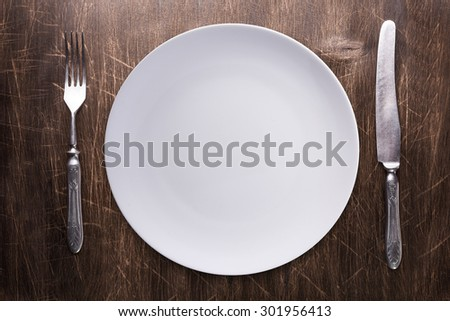 Empty plate, silverware over wooden table background. View from top with copy space.
