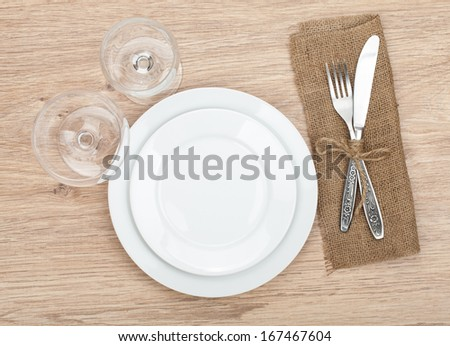 Empty plate, wine glasses and silverware set on wooden table - stock photo