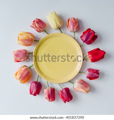 Empty plate with creative arrangement of tulip flowers on bright background. Flat lay. - stock photo
