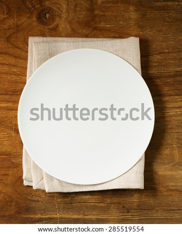 empty plate with cutlery and napkin on wooden background - stock photo