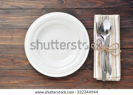 Empty plate with cutlery,fork and spoon on napkin on wooden background. - stock photo