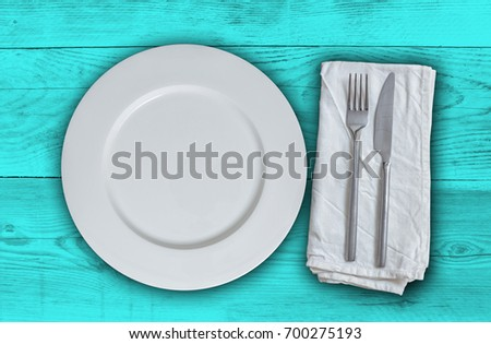 Empty plate with cutlery on petrol wood background.