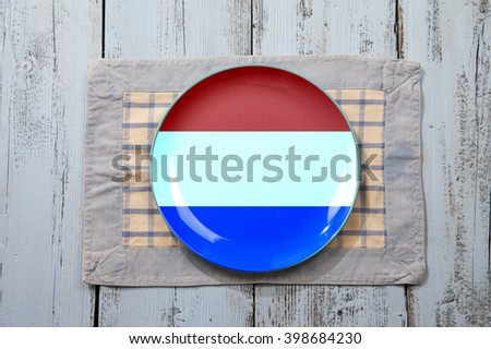 Empty plate with Dutch flag on light blue wooden background - stock photo