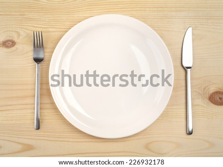 empty plate with fork and knife on the wooden table - stock photo