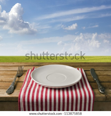 Empty plate with fork and knife on wooden table against blue sky and meadow. Table arrangement. - stock photo