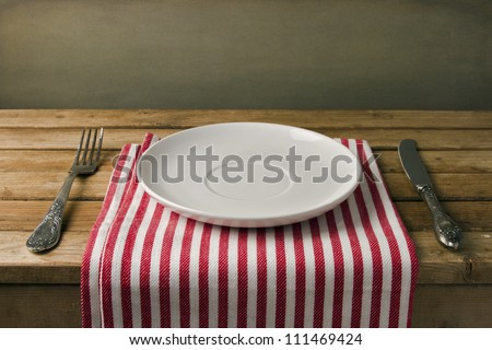 Empty plate with fork and knife on wooden table. Table arrangement. - stock photo