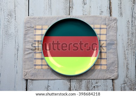 Empty plate with German flag on light blue wooden background - stock photo