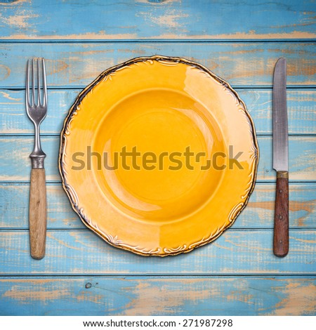 Empty plate with knife and fork on blue wooden table - stock photo