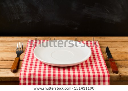 Empty plate with knife and fork on tablecloth on wooden table over chalkboard background - stock photo