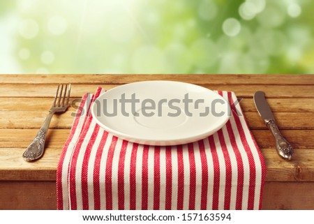 Empty plate with knife and fork on tablecloth over garden bokeh background - stock photo