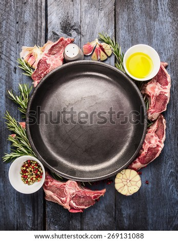 Empty plate with raw lamb loin chops meat , oil, herb and spices on  blue wooden background, top view - stock photo