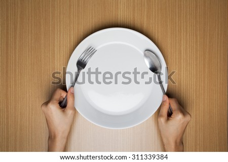 Empty plate with spoon and fork on wooden background - stock photo