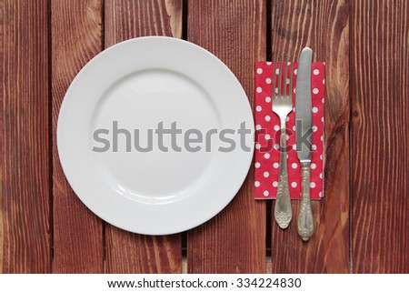 Empty plate with vintage fork and knife lying on a paper napkin