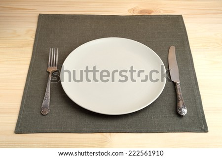 Empty plate with vintage fork and knife on green linen napkin on a wooden table - stock photo