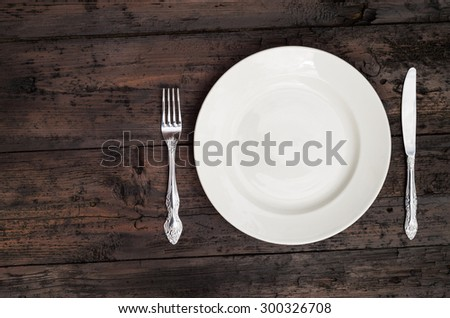 Empty plateh on wooden table - stock photo