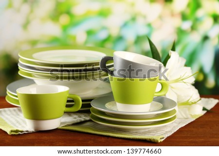 Empty plates and cups on wooden table on green background - stock photo