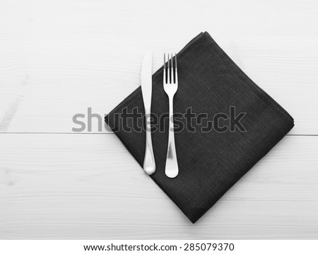 Empty plates and cutlery on table cloth on wooden table for dinner in restaurant. Flat mock up for design menu. Top view. - stock photo