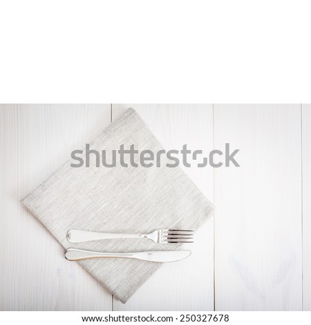 Empty plates and cutlery on table cloth on wooden table for dinner. Top view horizontally. - stock photo