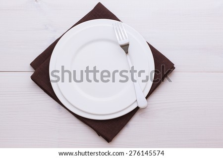 Empty plates and cutlery on table cloth on wooden table for dinner. Top view horizontally. Mock up for design.