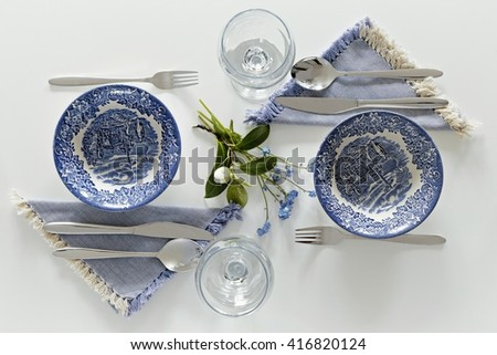 Empty plates and glasses, romantic dinner for two. Homey atmosphere clean white table. Top view - stock photo