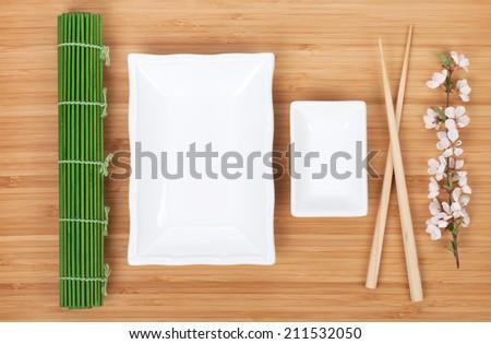 Empty plates, chopsticks and sakura branch over bamboo table - stock photo