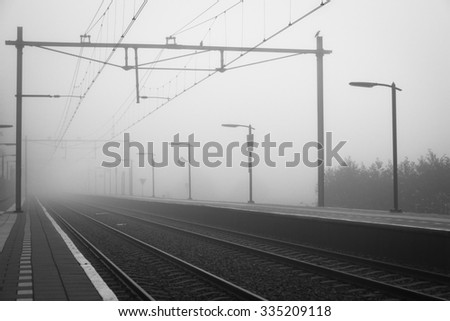 Empty platform and overhead wires disappearing into the fog at a railway station on a autumn day. - stock photo