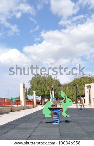 Empty Playground Equipment Outdoor Park Blue Sky Clouds Daytime - stock photo
