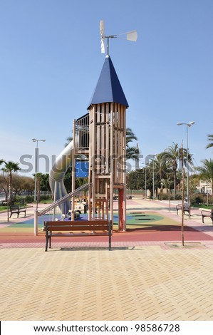 Empty Playground Jungle Gym Equipment with Windmill at Peak with bench in outdoor park area - stock photo