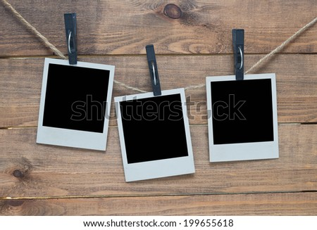 empty polaroid photo frames on wooden background - stock photo
