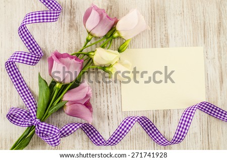 Empty postcard with flower and purple ribbon on wooden background - stock photo