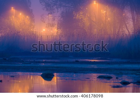 Empty promenade by foggy night illuminated with lampposts, selective focus - stock photo