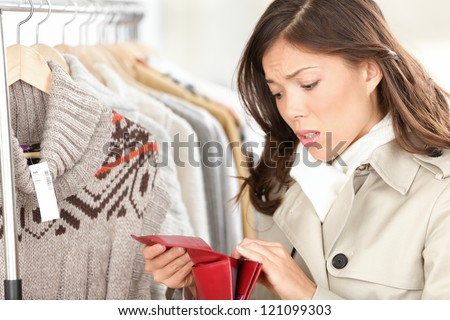 Empty purse or wallet - no money for shopping concept. Woman shopping for clothing in clothes store.