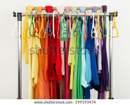 Empty rack of clothes and hangers after a big sale. Sale sign for summer clothes on a clearance rack with colorful summer outfits and accessories. - stock photo