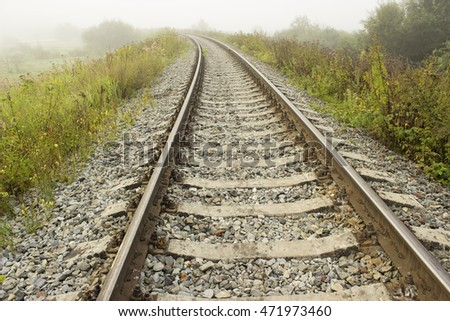 Empty railroad track going into a fog. Perspective view.