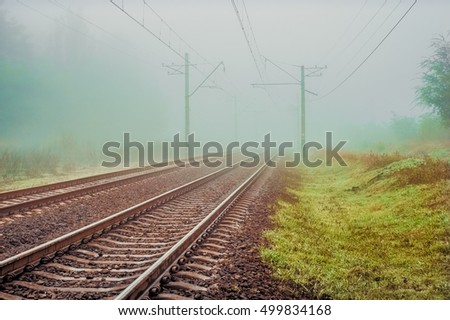 Empty railroad track going into a fog. Vintage toned photo background with tonal correction, old style effect.