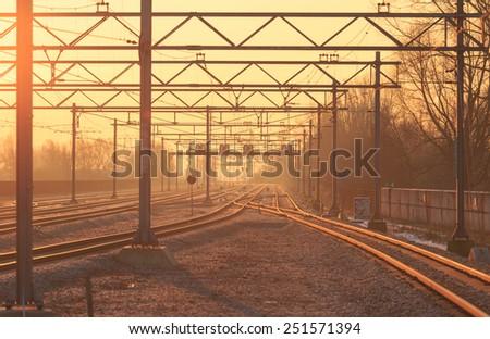 Empty railroad tracks during sunrise. - stock photo