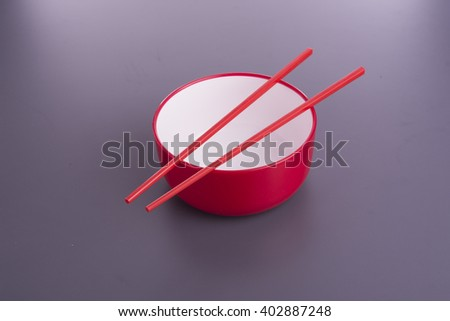 empty red bowl with red chop sticks on purple table - stock photo