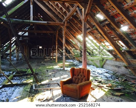Empty red chair in an destroyed and abandoned old house. The sunlight is falling through the wholes in the roof.