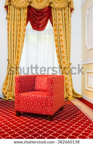 Empty red chair in the room with vintage red carpet and classic yellow drapes - stock photo